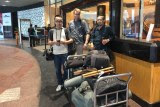 Lipson, Wu and Guilianno with trolley loaded    with gear outside hotel.