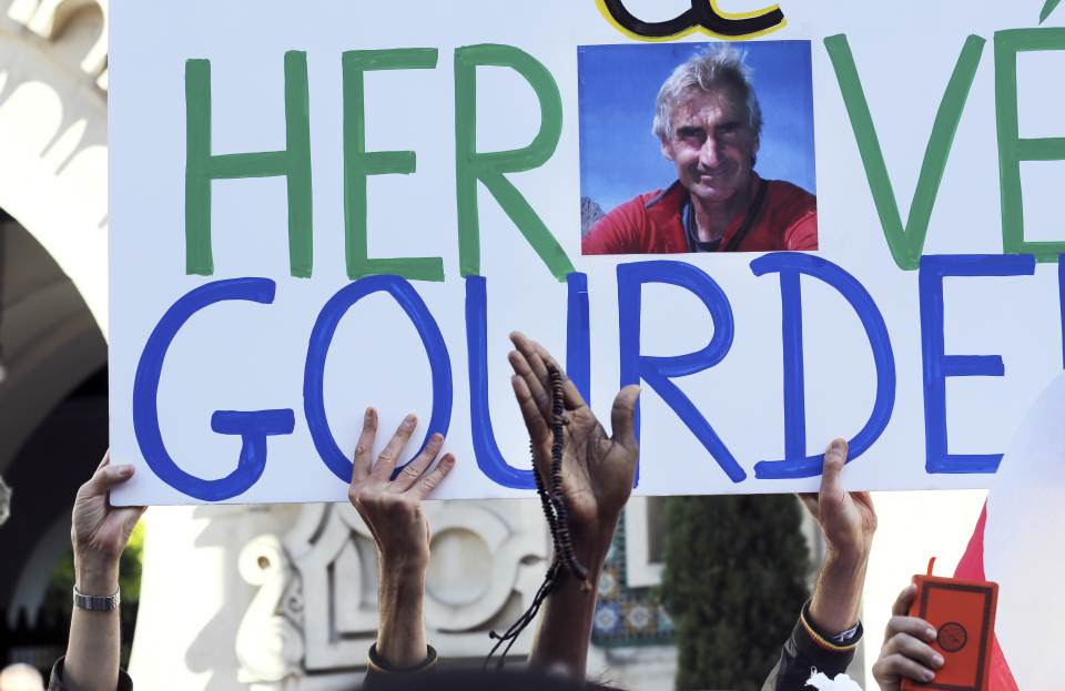 Muslims hold a sign paying homage to French mountaineer Hervé Gourdel, his photo in the centre of the banner, who was beheaded by Islamist militants...