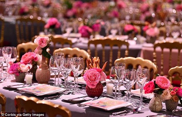 Elegante: As longas mesas foram decoradas com frascos de flores rosa vibrantes, retratadas