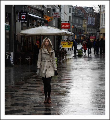 dame in natte straat by hans van egdom