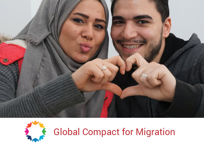 Compact for migration - man and woman make a heart symbol with their hands