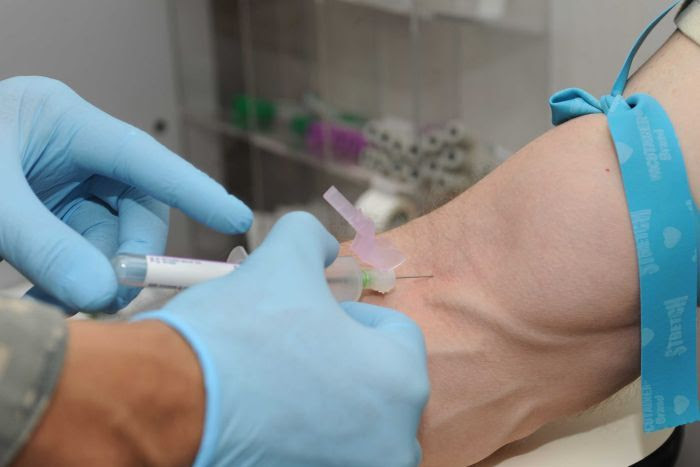 A patient gets blood drawn to be screened as a blood donor.