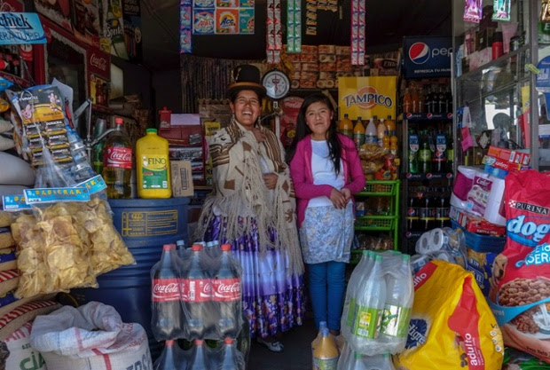 Lucia Mayta, 43, and her daughter Luz Cecilia, 12, pose for a photograph inside their bodega in La Paz, Bolivia. Lucia studied until the fourth grade of primary school, and knows how to read and write and do basic maths. She runs a bodega, and the family live in a back room. She hopes to build a house in the future. Luz Cecilia is in seventh grade and wants to be a singer.