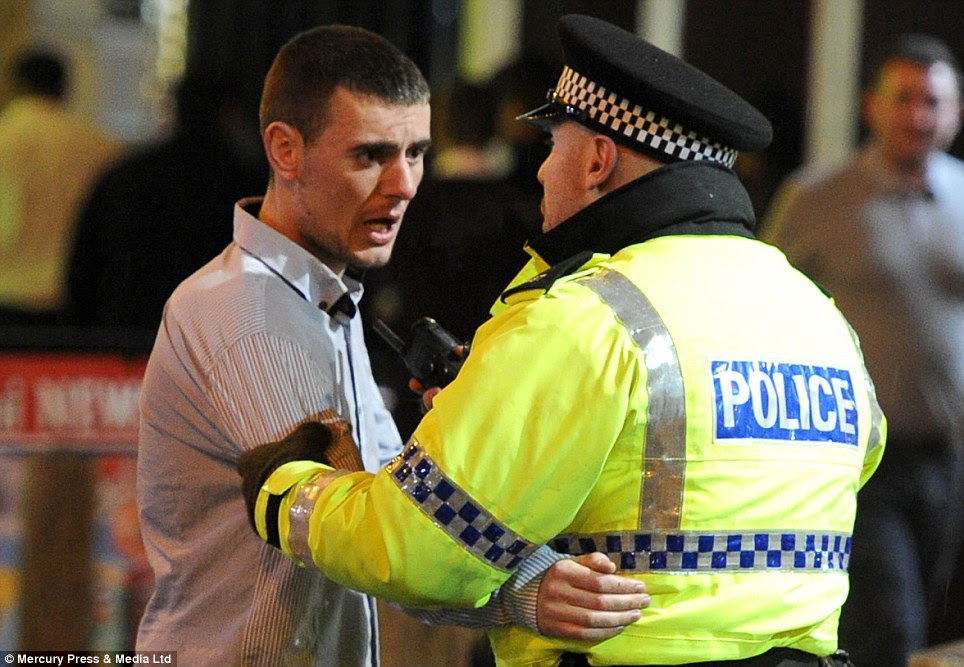 Chat: This police officer grabs this man by the arm and points his radio at him in Liverpool last night as people had a night out to celebrate the start of 2014