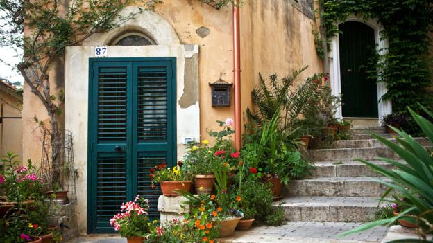 Flowers line the steps of an old Sicilian home (Credit: Credit: Thibaut Petit-Bara/Alamy)