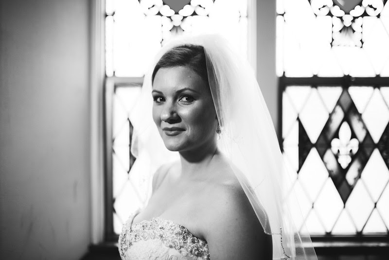 A bride in front of a stained glass window before her wedding at Court Street United Methodist Church in downtown Rockford Illinois for an Autumn wedding.