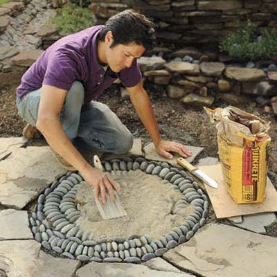 Mark Powers spreading topping mix over his pebble mosaic