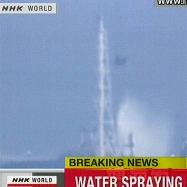Imagem da TV japonesa mostra helicóptero militar lançando água sobre o reator 3 na manhã desta quinta (17) (Foto: AFP)