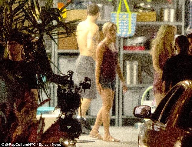 Tudo em um dia de trabalho: A atriz mais tarde foi descoberto em alguns shorts jeans casuais e parte superior roxa, piscando seu quadro de pernas longas como ela conversou com o diretor no set ao lado de um homem sem camisa muscly