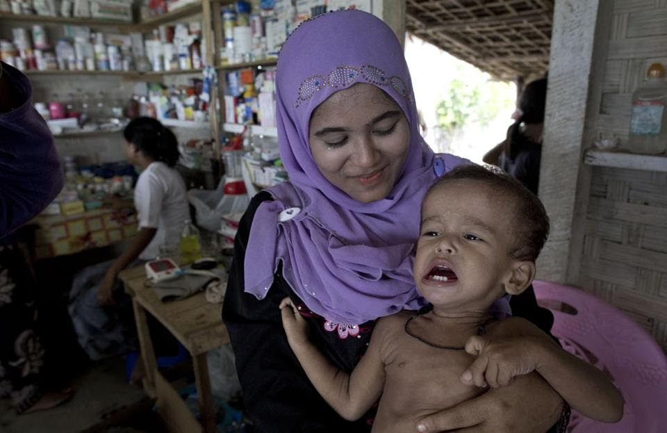 A woman comforted her child while waiting in a village pharmacy.