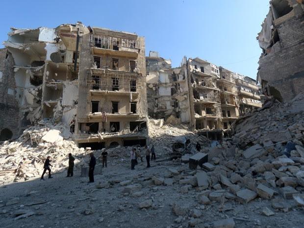 Sírios observam destruição em Shaar, a nordeste de Aleppo, neste sábado (Foto: AFP)