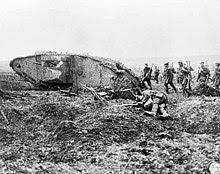 Sepasukan askar bersenapang berarak di atas tanah yang tidak rata melalui kereta kebal yang hancur dan mayat seorang askar