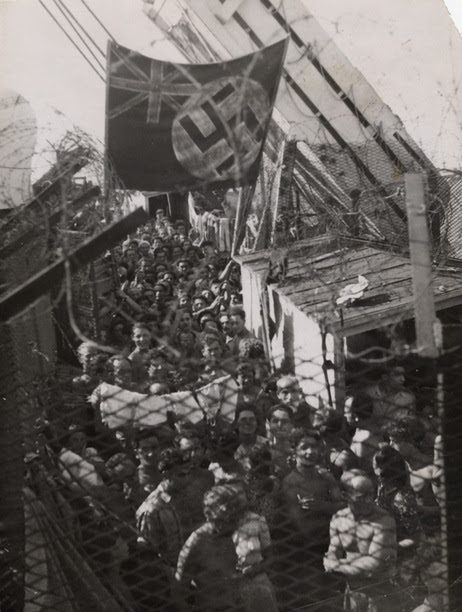 1,500 Jewish refugees, having been forced off Exodus 1947 in Haifa, Palestine, wait aboard the British prison ship Runnymede Park. In protest, the prisoners painted a swastika on top of the Union Jack. August 22, 1947