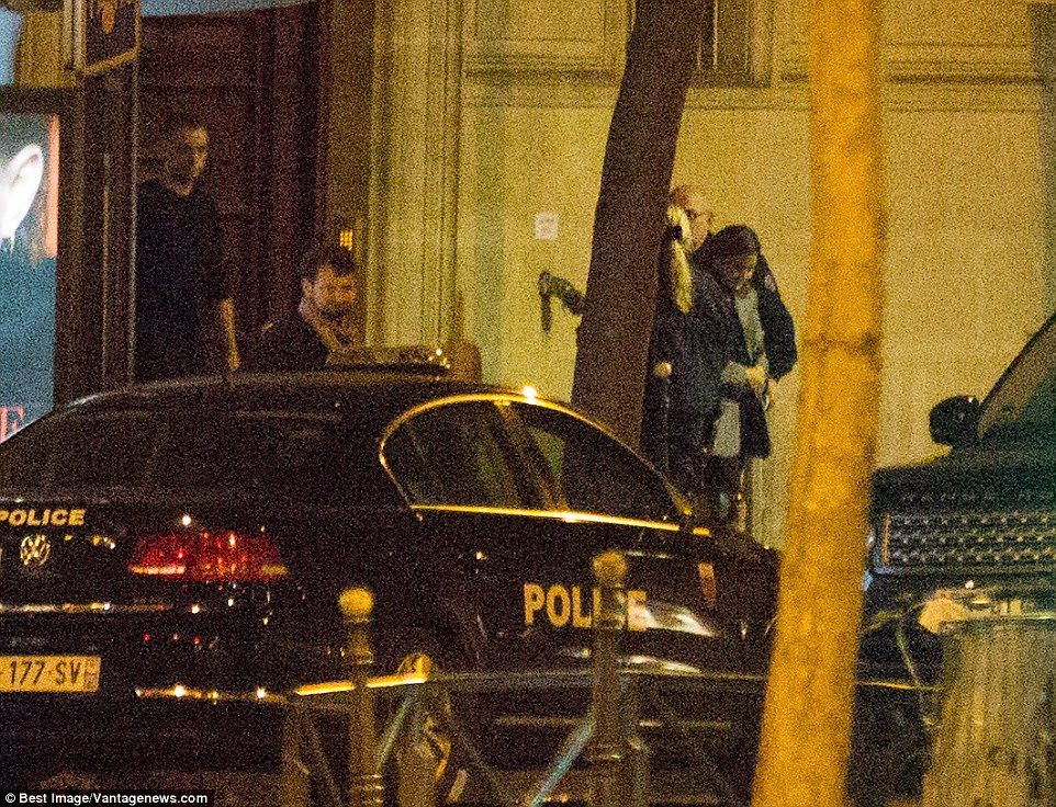 Uma mulher vestida com um casaco cinza foi levado para longe da cena por policiais na segunda-feira de manhã