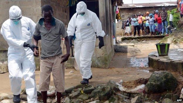 As enfermeiras usando roupas de proteção escoltar um homem infectado com o vírus Ebola em um hospital em Monrovia, Libéria - 25 de agosto de 2014
