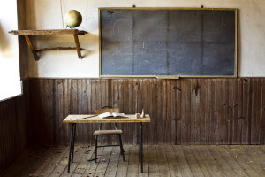 An old classroom is shown with an empty desk