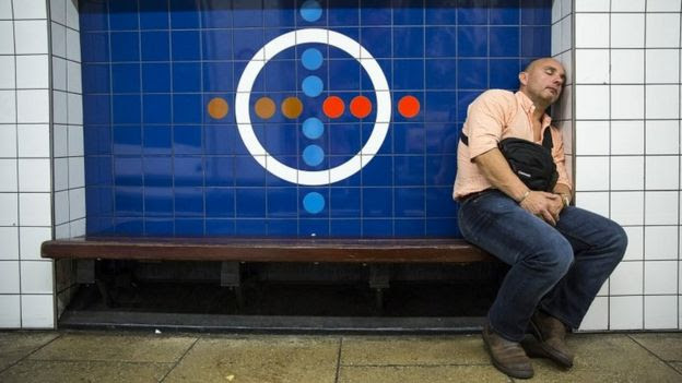 A passenger rests on a bench at Oxford Circus Underground station