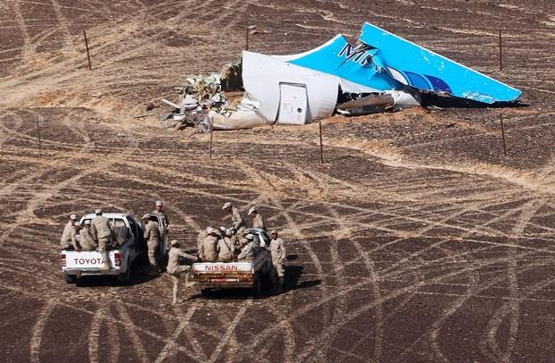 Militares egípcios vistoriam a cauda do avião russo que caiu na Península do Sinai; a foto foi divulgada no dia 2 de novembro de 2015 pelo Ministério das Situações de Emergência russo (Foto: Maxim Grigoriev/Russian Ministry for Emergency Situations/AP)