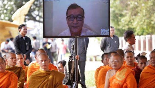 Sam Rainsy speaks to supporters in Phnom Penh yesterday via a video link.