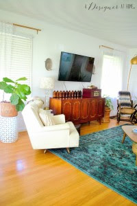 Entering a casually boho eclectic decorated space the living room of a 1950's brick ranch