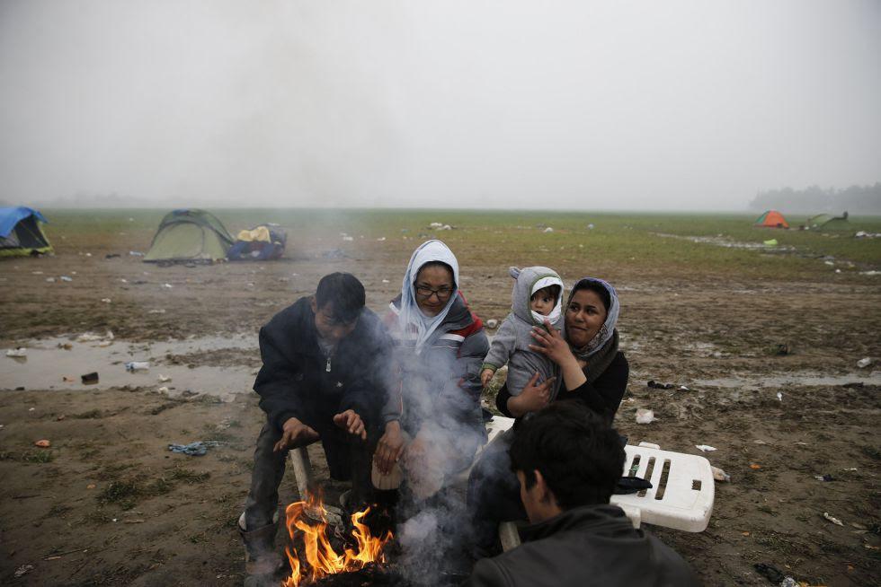 Migrantes afganos se calientan en una hoguera el campo de refugiados de Idomeni, en la frontera entre Grecia y Macedonia.