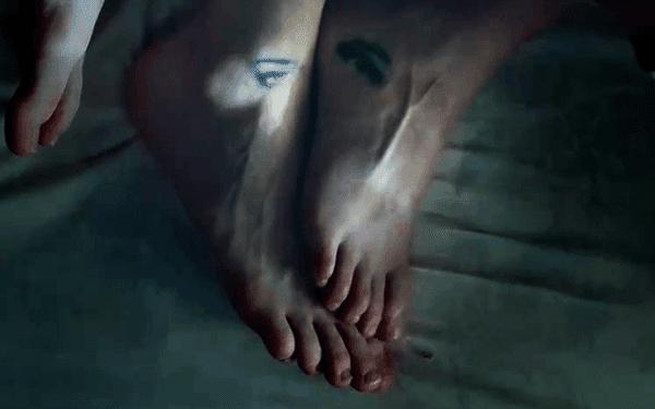 """Em um tiro, vemos o casal, que togheter com os pés exibindo uma tatuagem harmonização ... de olhos.  Embora esta parece ser uma coisa romântica, quando aprendemos sobre a relação escravo / manipulador, a tatuagem """"olho que tudo vê"""" assume um significado perturbador."""