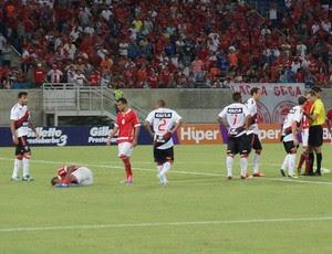 Isac (no chão), atacante do América-RN, após sofrer falta do goleiro Wilson, do Vitória (Foto: Augusto Gomes)