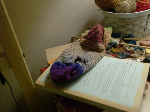 Handknit wool knitted handspun striped sock with a hole in it that needs darning