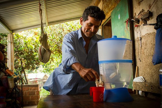 After a day working on the land where he grows corn and beans, Víctor de León serves himself freshly purified water, one of the benefits of the climate change adaptation project in the Central American Dry Corridor region, La Colmena village, in the municipality of Candelaria de la Frontera, in the western department of Santa Ana, El Salvador. Credit: Edgardo Ayala/IPS