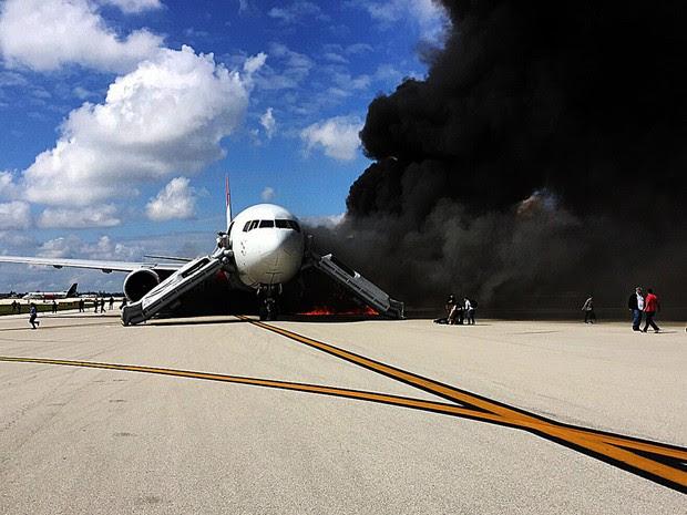 Passageiros deixam um avião em chamas no aeroporto de Fort Lauderdale, na Flórida, EUA. O avião pegou fogo em uma pista do aeroporto e várias pessoas ficaram feridas, informaram as autoridades (Foto:  Andres Gallego/AFP)