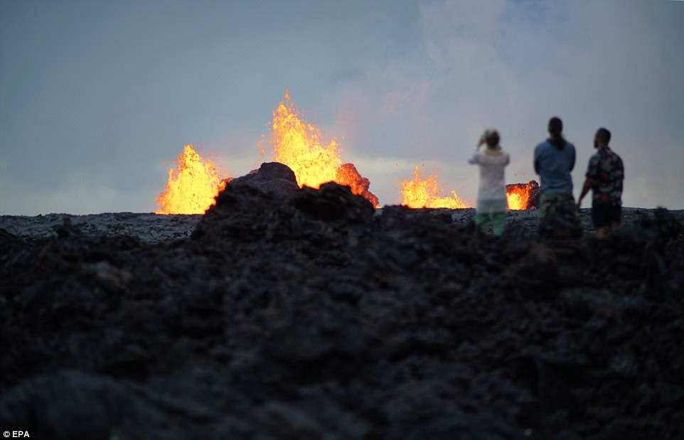 Community members who lost their property to the volcanic activity looking watch the fissure at dusk on Hawaii Island