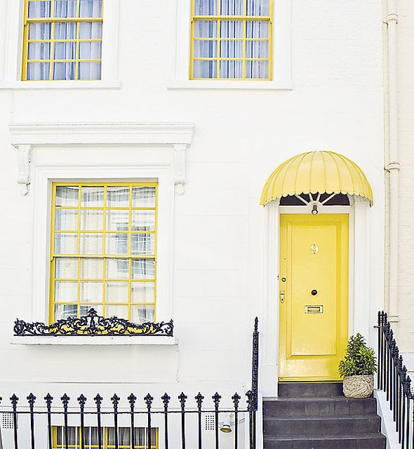 Notting Hill. Yellow door, yellow awning and yellow window frames with black wrought iron detailing
