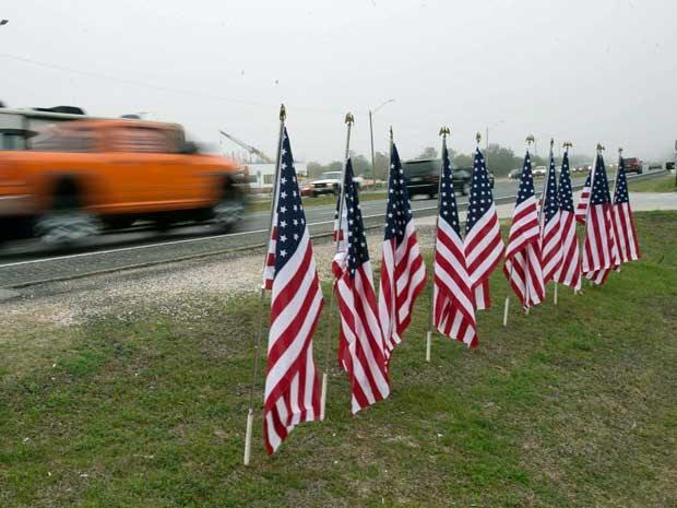 Onze bandeiras fincadas em estrada homenageiam grupo de militares mortos após queda de helicóptero na Flórida. (Foto: Michael Spooneybarger / Reuters)