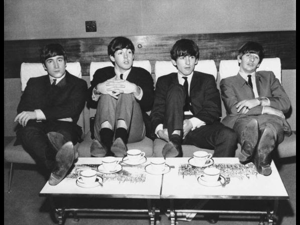 The Beatles, Britain's top rock band, relax in London over tea in 1963. The group from left: John Lennon, Paul McCartney; George Harrison and Ringo Starr. The group is sporting similar thatch haircuts with bangs to the edge of their eyebrows. No other information available with photo.