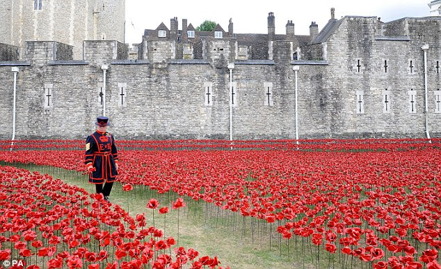 Yeoman Serjeant Bob Loughlin walks through a mass of ceramic poppies which form the Blood Swept Lands and Seas of Red tribute at the Tower of London
