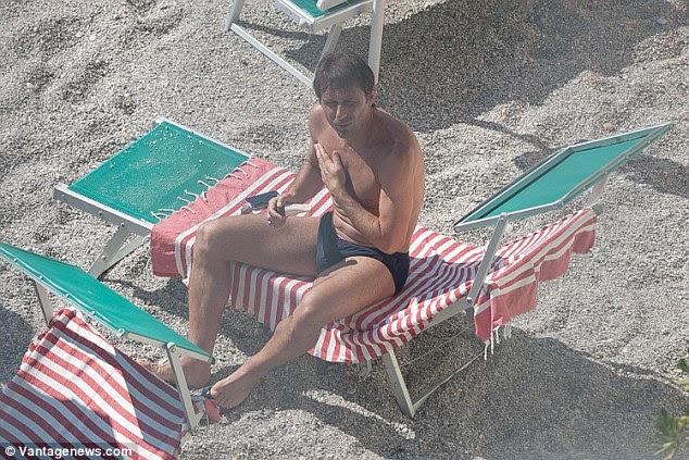 The 47-year-old Italian coach looks on from his sun bed during his much-deserved break