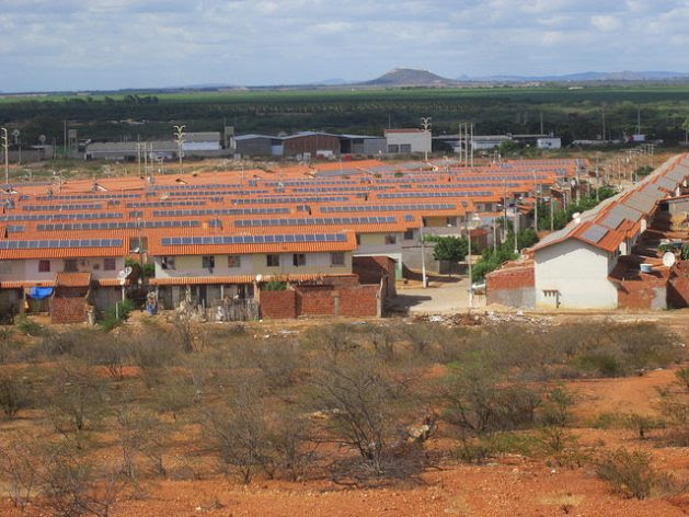 The social housing complexes of Morada do Salitre and Praia do Rodeadouro, with solar panels on their rooftops, make up a village of 1,000 families on the outskirts of the city of Juazeiro, in the Brazilian state of Bahia. A solar energy project, which has been suspended, created jobs for local residents to plant trees and clean the streets. Credit: Mario Osava/IPS