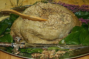 Haggis on a garnished platter with the knife u...