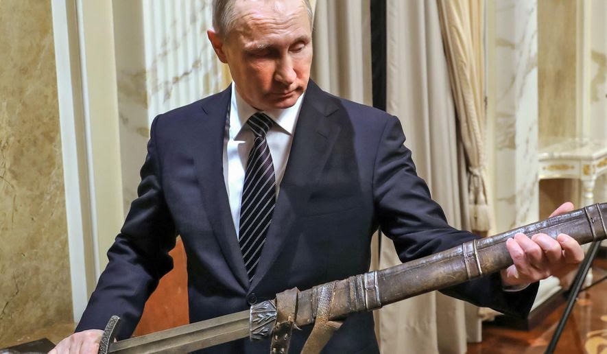 Russian President Vladimir Putin holds a sword while listening an explanations from the head of Russian First Channel Konstantin Ernst, during his meeting with the historical action film Viking's crew, in Moscow, Russia, Friday, Dec. 30, 2016.  Viking is a historical action film based on the historical document Primary Chronicle and Icelandic Kings' sagas. (Mikhail Klimentyev, Sputnik, Kremlin Pool Photo via AP)