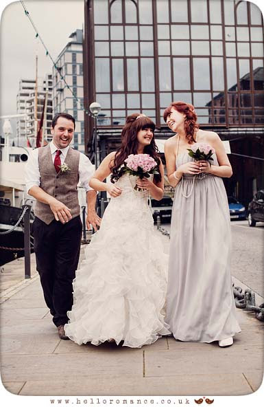 Bride and Groom with Bridesmaid walking and having fun at Isaac Lord Ipswich Waterfront Isaac's Suffolk Unique Vintage wedding photography - Hello Romance Wedding Photography