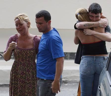 Regina Célia Ribeiro, viúva de Hélio (à direita), é amparada por parentes