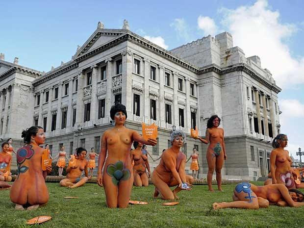 Mulheres nuas e com os corpos pintados realizam manifestação na frente do Parlamento uruguaio. (Foto: Matilde Campodonico / AP Photo)