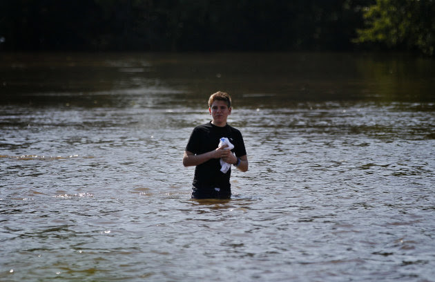 Nick Grassett walks through floodwater that rose above the banks of the St. Jones River in Dover, Del., Sunday, Aug. 28, 2011, after Hurricane Irene dumped several inches of rain along the Delaware co