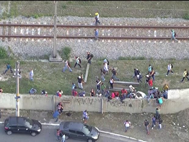 Passageiros pulam muro após trem parar entre estações da CPTM  (Foto: Reprodução/TV Globo)
