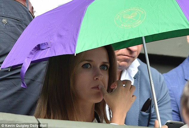Kim Murray watches on from under an umbrella as Murray battles for a place in the fourth round at Wimbledon