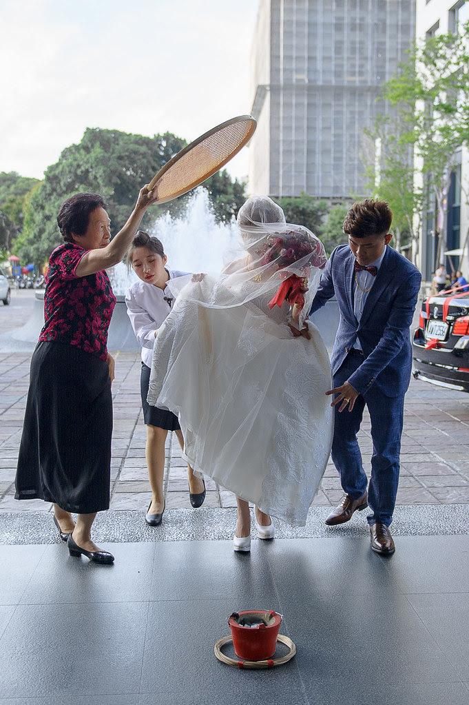 107媒人持米篩遮於新娘與新郎陪同新娘走出大廳