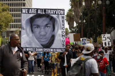 Varios manifestantes portan una pancarta con una fotografía de Trayvon Marti, en Los Angeles.- DAVID MCNEW (REUTERS)