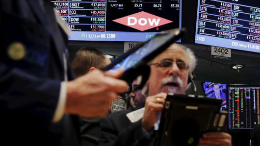 Traders work below a board displaying the Dow Chemical logo on the floor of the New York Stock Exchange.