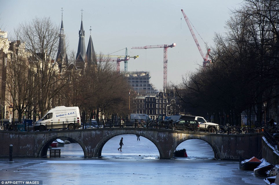 Making use: People skate across frozen canals in Amsterdam, the Netherlands, which have been closed to commercial shipping