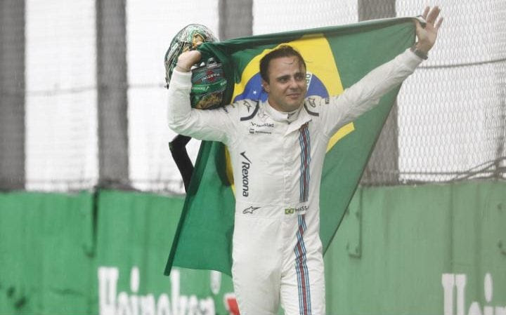 Felipe Massa carries a Brazilian flag and waves to the fans as he walks back to his garage in tears after crashing out of the race